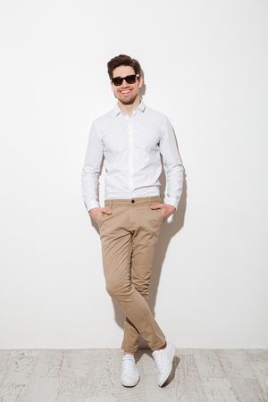 Full length photo of handsome guy dressed in casual clothing and sunglasses smiling while standing with hands in pockets and looking on camera over white wall with shadow Stock Photo
