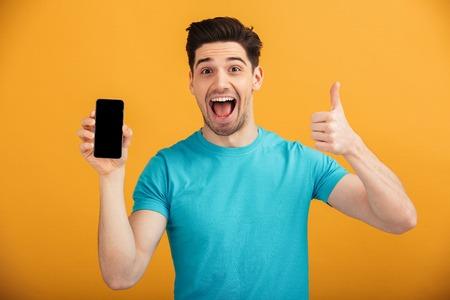 Retrato de un joven feliz en camiseta con teléfono móvil de pantalla en blanco y mostrando los pulgares arriba aislado sobre fondo amarillo