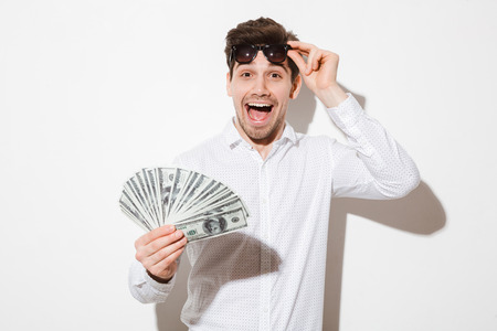 Splendid photo of excited man in shirt taking off black sunglasses and enjoying fan of money dollar bills with pleasure and joy isolated over white wall with shadow