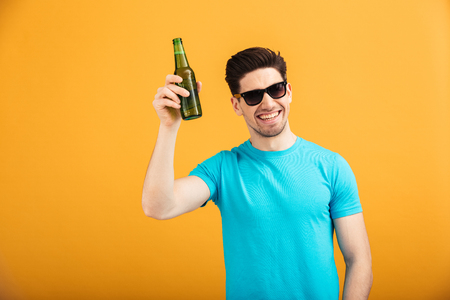 Portrait of a satisfied young man in sunglasses holding beer bottles isolated over yellow background