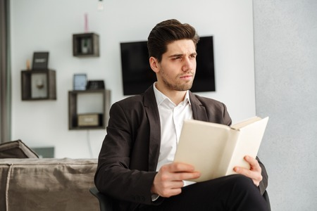 Photo of serious young businessman sitting in home indoors. Looking aside reading book.