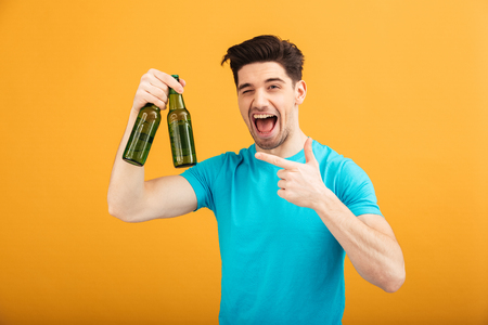 Portrait of a happy young man in t-shirt holding beer bottles and pointing finger isolated over yellow background