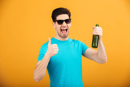 Portrait of a cheerful young man in t-shirt holding beer bottles and showing thumbs up gesture isolated over yellow background Stock Photo