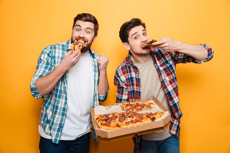 Two cheerful men in shirts eating pizza and looking at the camera over yellow background