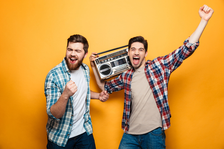 Two playful men in shirts listening music by record player while rejoices and looking at the camera over yellow background Stock Photo