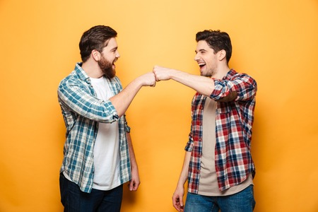 Portrait of a two happy young men giving fist bump isolated over yellow background Banque d'images