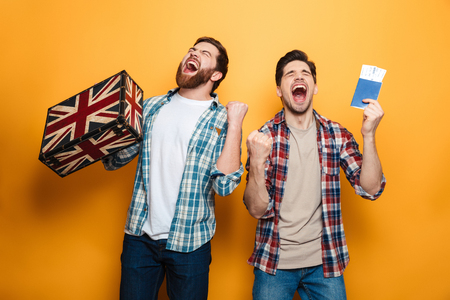 Two screaming men in shirts preparing to trip while rejoices with closed eyes over yellow background Stock Photo