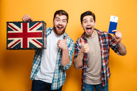 Two happy intrigued menn in shirts preparing to trip and showing thumbs up while holding passport with suitcase and looking at the camera over yellow background Stock Photo