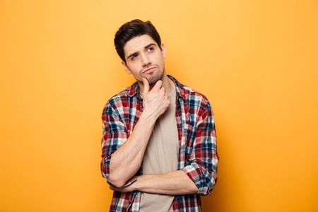 Portrait of a pensive young man looking away at copy space isolated over yellow background