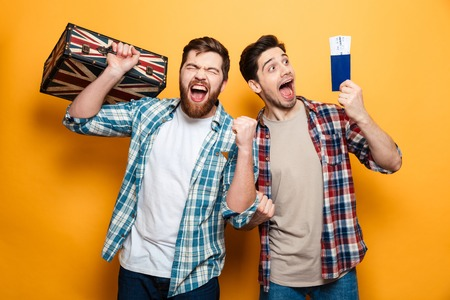 Two happy men in shirts standing with suitcase and passport preparing to trip while looking at the camera over yellow background