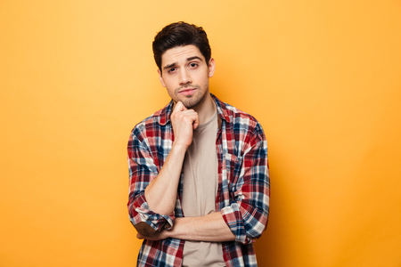 Portrait of a pensive young man looking at camera isolated over yellow background