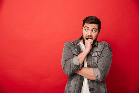 Image of scared man 30s in jeans jacket looking aside on copyspace and biting his fist in horror or fright isolated over red background Stock Photo