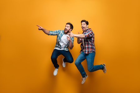 Full length portrait of a two excited young men pointing fingers away while jumping isolated over yellow background