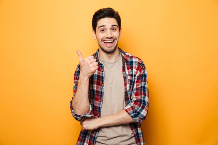 Portrait of a smiling young man pointing finger away at copy space isolated over yellow background Banco de Imagens