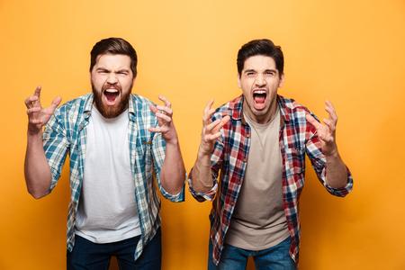 黄色の背景に隔離された大声で叫ぶ2人の怒っている若い男性の肖像画