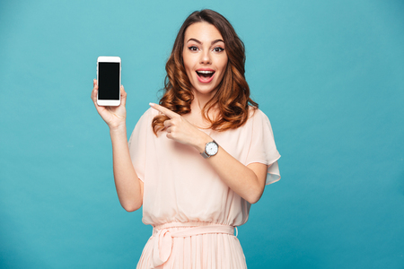 Portrait of an excited beautiful girl wearing dress pointing finger at blank screen mobile phone isolated over blue background Foto de archivo