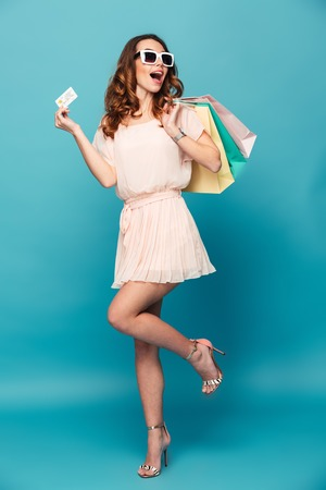 Full length portrait of a happy beautiful girl wearing dress and sunglasses holding shopping bags and showing credit card isolated over blue background