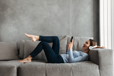 Portrait of a cheerful young woman listening to music with headphones and using mobile phone while resting on a couch at home