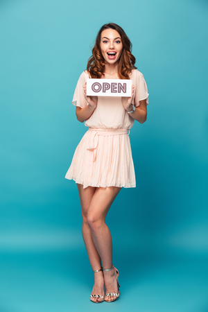 Full length portrait of a lovely beautiful girl wearing dress and showing an open sign isolated over blue background
