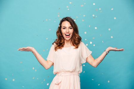 Portrait of a happy beautiful girl wearing dress standing standing under confetti rain and celebrating isolated over blue background Imagens