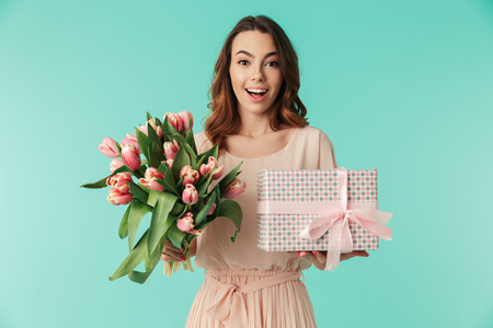Portrait of a satisfied young girl in dress holding pink tulips bouquet and present box isolated over blue background Stock Photo