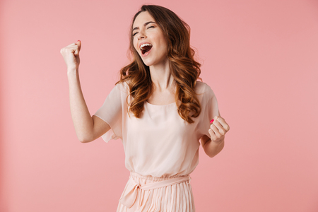 Portrait of a happy young girl in dress celebrating success isolated over pink background