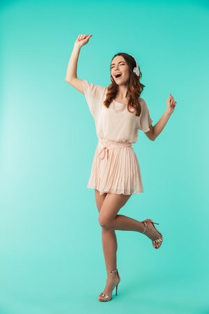 Full length portrait of a happy young girl in dress listening to music with headphones and dancing isolated over blue background