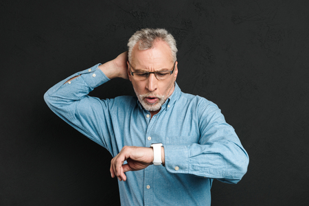 Image of elderly unshaved man 60s with grey hair wearing eyeglasses looking at his wrist watch with confusion isolated over black background Stock Photo