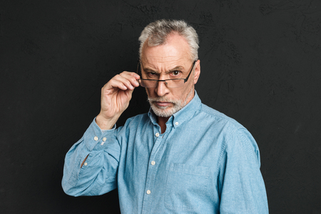 Horizontal photo of mature unshaved man 60s with grey hair wearing eyeglasses looking on camera with severe gaze and touching eyeglasses isolated over black background