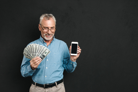 Photo of caucasian retired man 60s with gray hair holding mobile phone and lots of money dollar currency isolated over black background Stock Photo