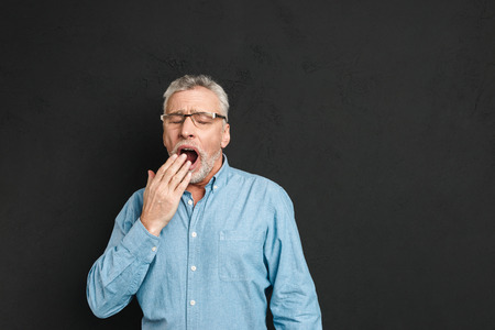 Horizontal photo of mature unshaved man 60s with grey hair wearing eyeglasses being sleepy and yawning because of insomnia isolated over black background