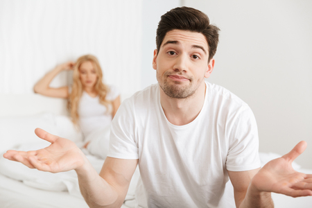 Image of young loving couple in bed indoors at home quarrel. Focus on confused man. Stock Photo