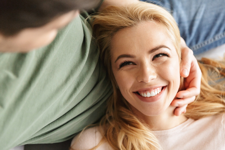 Photo of cute smiling young woman lies on her husband indoors at home. Stock Photo