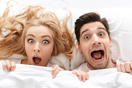 Photo of shocked young loving couple lies in bed covering faces under blanket.