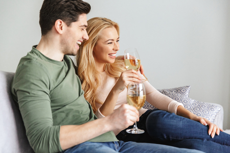 Picture of smiling young loving couple indoors at home drinking alcohol white wine champagne.