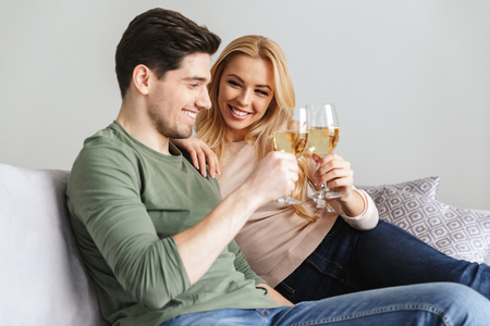 Photo of happy young loving couple sitting on sofa indoors at home drinking alcohol white wine champagne.