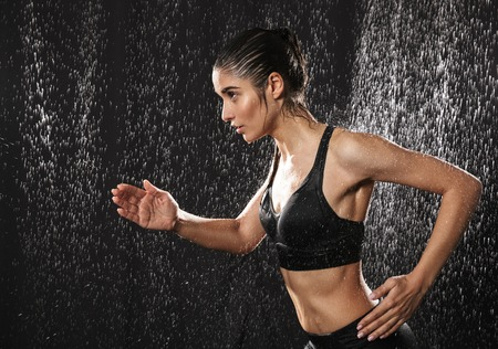 Portrait of a healthy young sportswoman running under the rain over black background Stock Photo