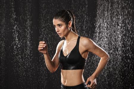 Portret van een geconcentreerde jonge sportvrouw die onder de regen over zwarte achtergrond loopt Stockfoto
