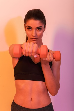Photo of serious young sports woman make exercises with dumbbells isolated over wall background. Looking camera.