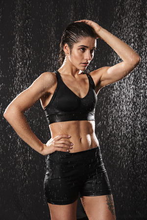 Portrait of a fit young sportswoman posing while standing under the rain over black background