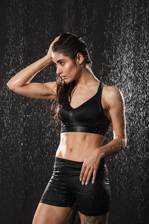 Portrait of a sexy young sportswoman posing while standing under the rain over black background 版權商用圖片