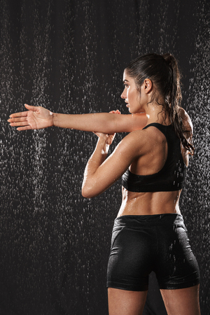 Photo from back of concentrated slim woman in sports clothing stretching her arms while standing under the rain drops isolated over black background