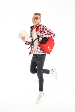 Full length portrait of happy educated teenage boy wearing plaid shirt smiling and looking on camera isolated over white background Stock Photo