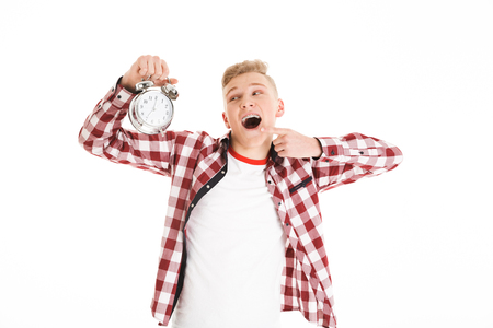 Photo of pleased teen man 17y wearing plaid shirt holding alarm and pointing finger on clock face isolated over white background