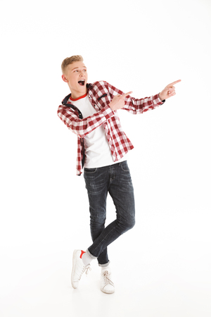 Full length photo of excited teen man 17y wearing plaid shirt exclaiming and pointing fingers aside on copyspace isolated over white background