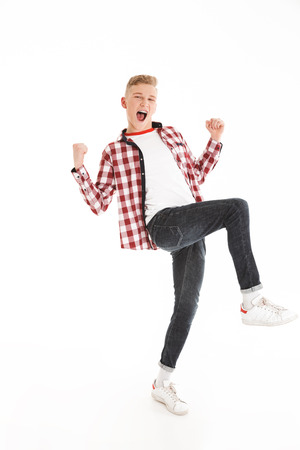 Full length portrait of happy teenage boy wearing plaid shirt smiling and clenching fists on camera like winner or smart pupil isolated over white background Stock Photo