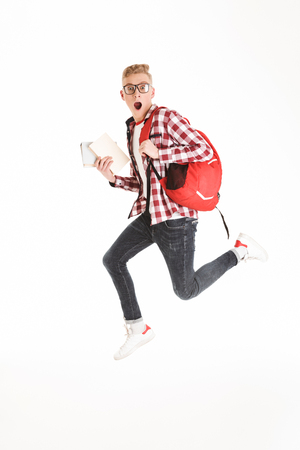 Full length portrait of a shocked schoolboy in eyeglasses with backpack holding books and jumping isolated over white background Stock Photo