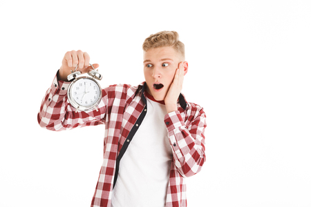 Picture of young hipster man 16y in casual holding and looking at alarm clock counting time for schedule isolated over white background Stock Photo