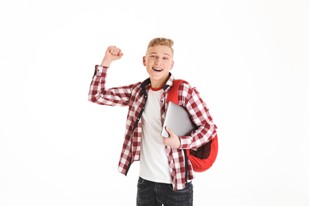 Portrait of attractive smart teenage boy wearing plaid shirt and braces posing with silver notebook and backpack while gesturing in joy isolated over white background
