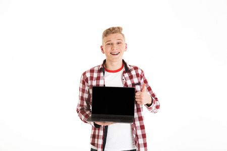 Teenager 18y wearing casual shirt holding silver notebook demonstrating or advertising copyspace screen and showing thumb up isolated over white background